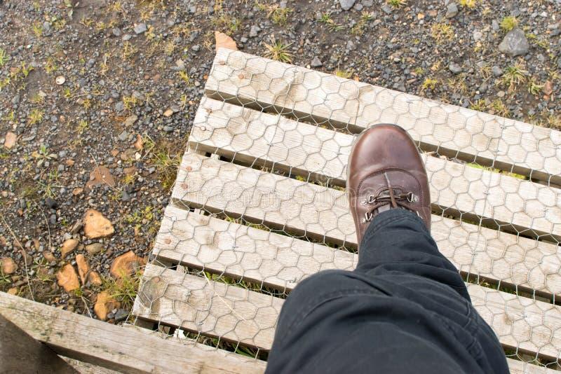 jambe faisant un pas au-dessus du montant en bois images libres de droits