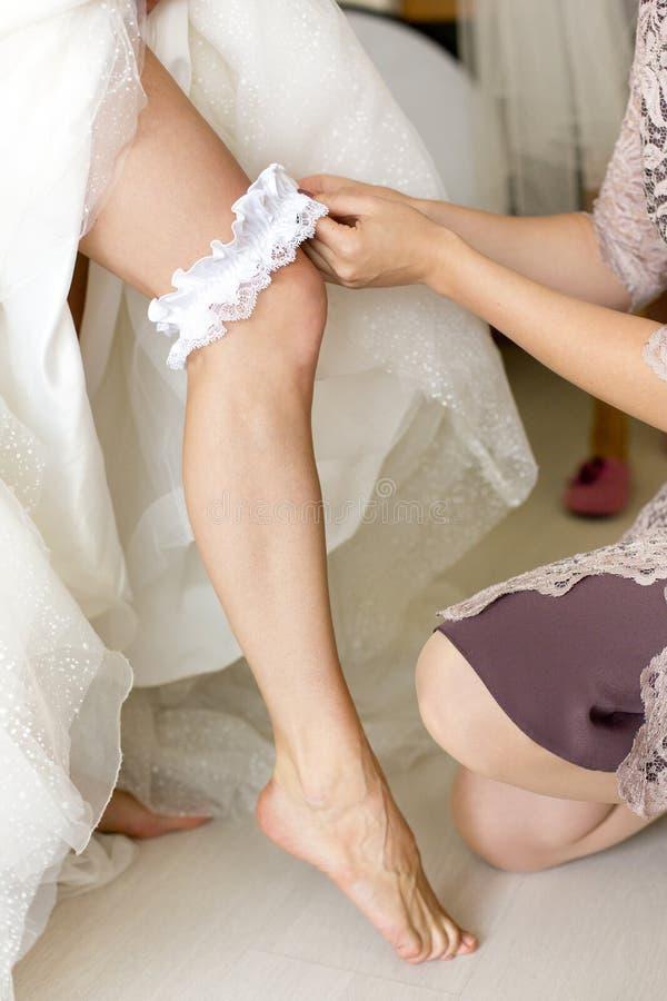 Jambe nue de jeune mariée ou fille ou femme avec la jarretière de mariage image stock