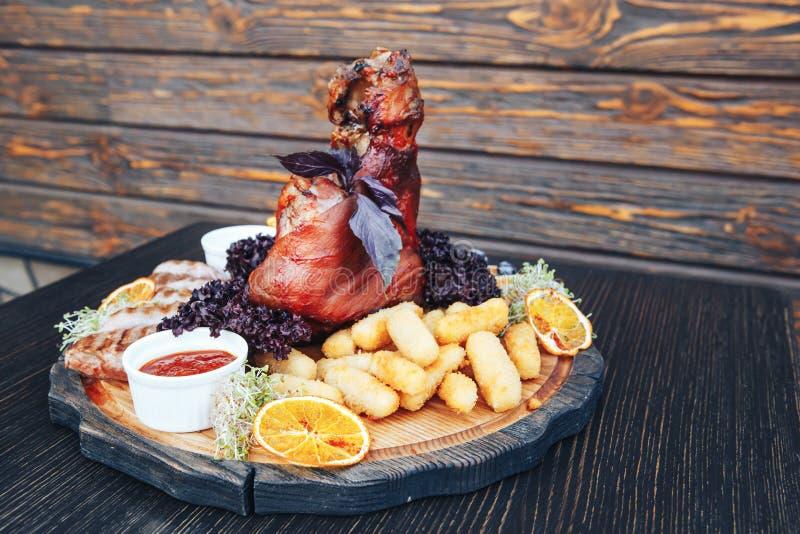 Jambe rôtie de porc ou d'agneau avec de la sauce Jambe frite de porc avec de la sauce sur un conseil en bois de coupe Fond en boi photos libres de droits
