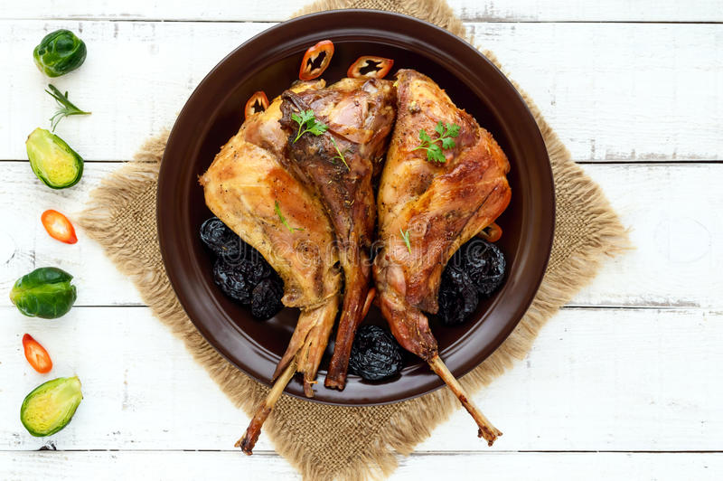 Jambe rôtie de lapin avec des pruneaux d'un plat en céramique sur le fond clair photos stock