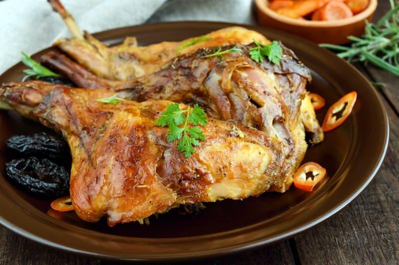 Jambe rôtie de lapin avec des pruneaux d'un plat en céramique sur le fond en bois foncé images stock