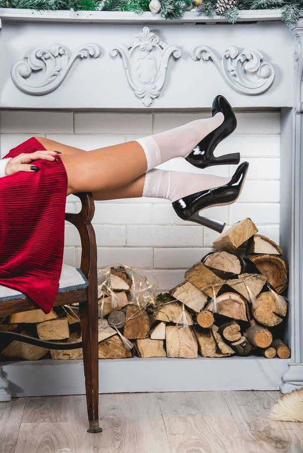 Jambes érotiques dans les chaussettes blanches et des chaussures noires Jeunes jambes femelles sur un fond de mur décoré par Noël photo stock