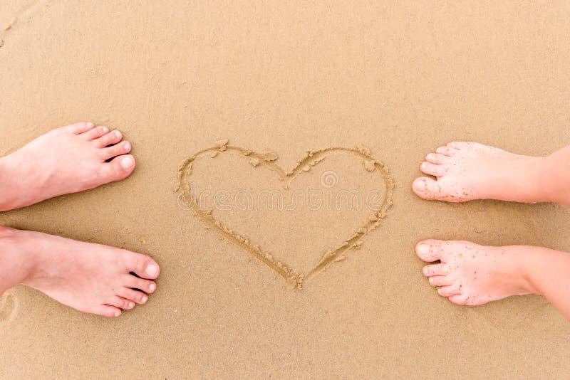 jambes aimant des couples nu-pieds sur le sable photos stock