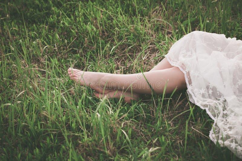 Jambes aux pieds nus de femme sur l'herbe photo stock