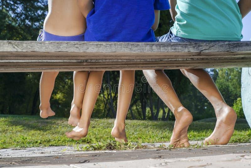 Jambes aux pieds nus de trois enfants s'asseyant sur le banc photo stock
