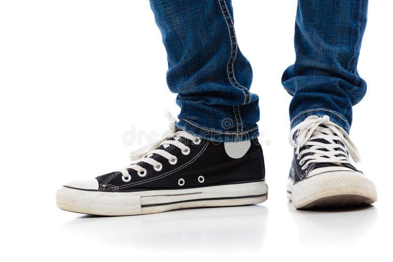 Jambes avec des chaussures et des jeans de tennis photos stock