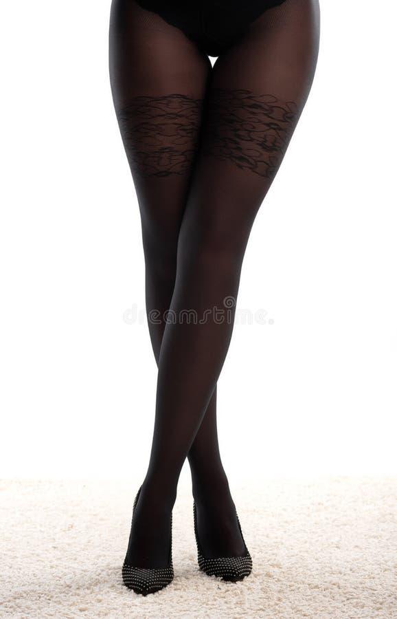Jambes avec les chaussures à talons hauts noires image stock