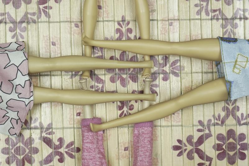 Jambes croisées de quatre poupées se trouvant sur le plancher photographie stock libre de droits