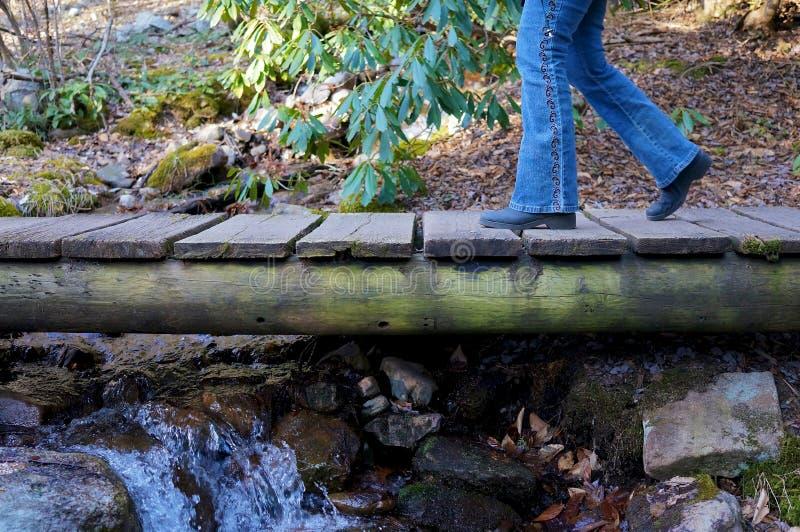 Jambes croisant le pont de pied image libre de droits
