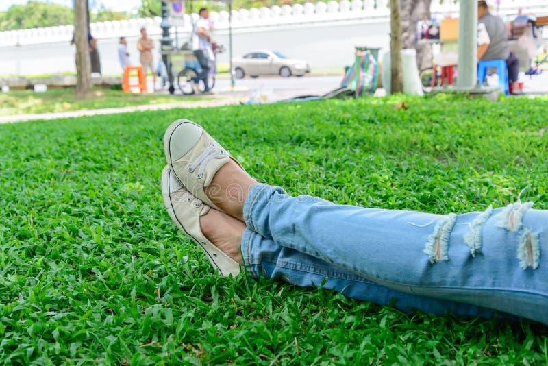 Jambes cultivées de femme en denim avec les espadrilles blanches se reposant sur l'herbe image libre de droits
