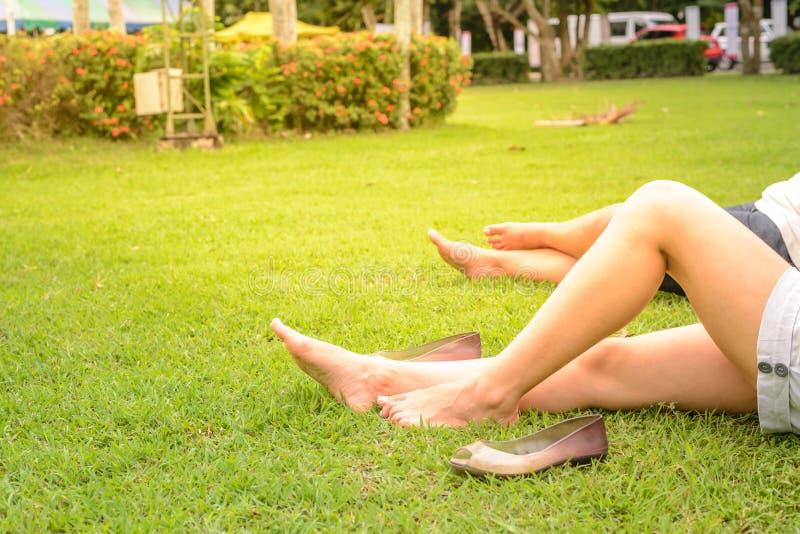 Jambes cultivées de femme se reposant sur l'herbe images libres de droits