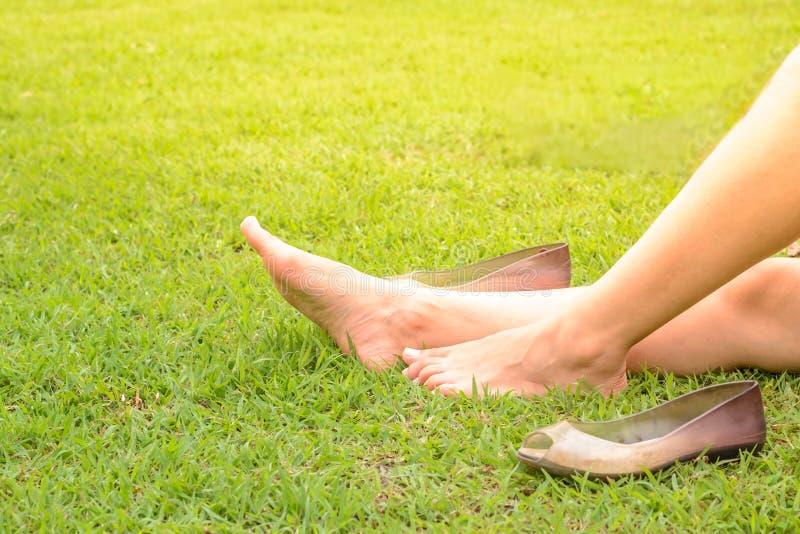 Jambes cultivées de femme se reposant sur l'herbe photo stock