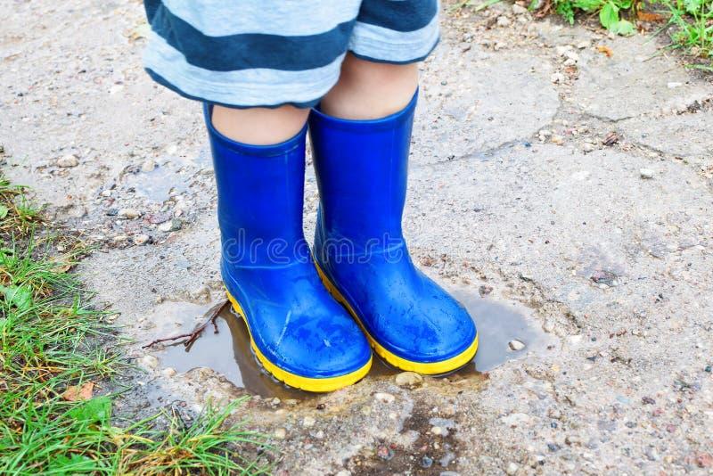 Jambes d'enfant dans des bottes en caoutchouc bleues image stock