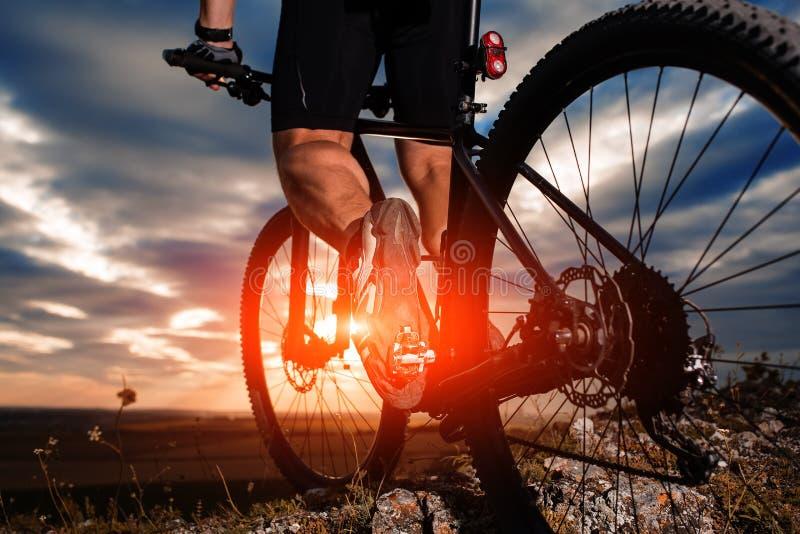 Jambes d'homme de cycliste montant le vélo de montagne sur la traînée extérieure photographie stock