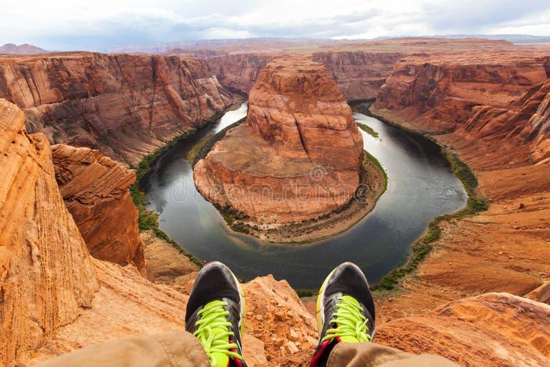 Jambes d'homme de voyageur se reposant sur le fond de la courbure en fer à cheval de canyon, Arizona, Etats-Unis Concept de voyag photographie stock