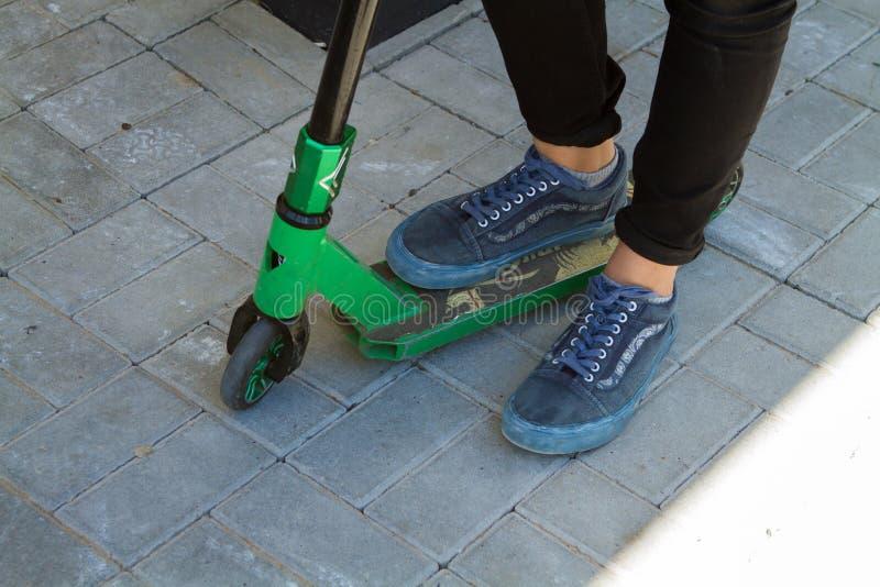 Jambes d'un adolescent dans des jeans noirs sur un scooter photos libres de droits