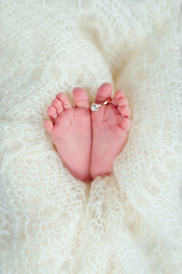 Jambes d'un bébé nouveau-né avec l'anneau l'épousant de la maman dans une couverture blanche chaude de laine Concept de la famill photos libres de droits