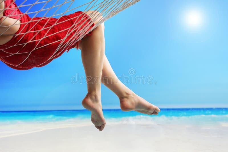 Jambes d'une femme se situant dans un hamac par la mer photos libres de droits