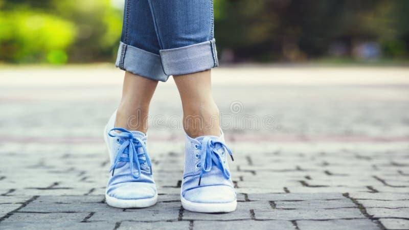 Jambes d'une fille dans les jeans et des espadrilles bleues sur une tuile de trottoir, une jeune femme flânant en parc d'été photographie stock libre de droits