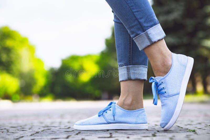 Jambes d'une fille dans les jeans et des espadrilles bleues sur une tuile de trottoir, une jeune femme flânant en parc d'été images stock