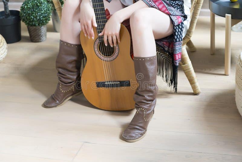 Jambes dans des bottes de cowboy en cuir et une guitare de sept-ficelle image stock
