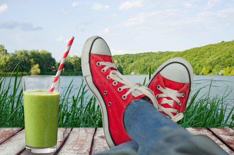 Jambes dans des chaussures de sport en vacances, avec vue sur la nature et un froid images libres de droits