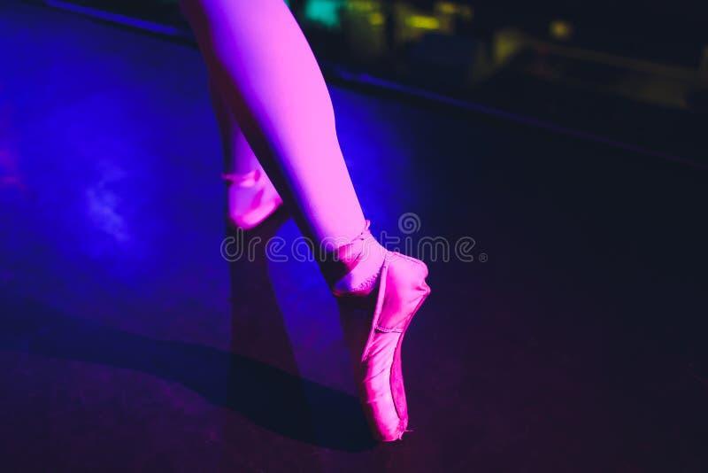 Jambes de ballerine dans les pointes sur le plancher de parquet sur le fond fonc? photos stock