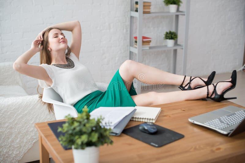 Jambes de détente de repos de femme d'affaires sur les mains de table derrière sa tête et reposer une chaise dans le bureau images stock