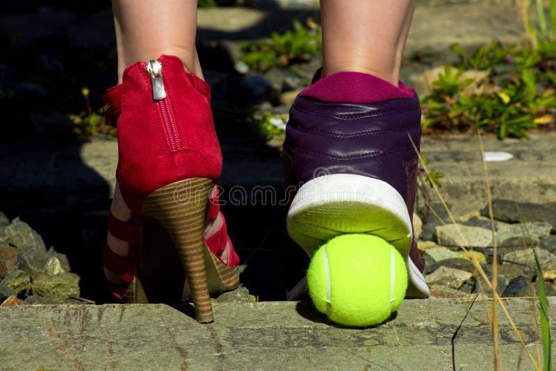 Jambes de dames, un pied dans la chaussure de cour et l'autre pied dans une chaussure de sports et une balle de tennis images stock