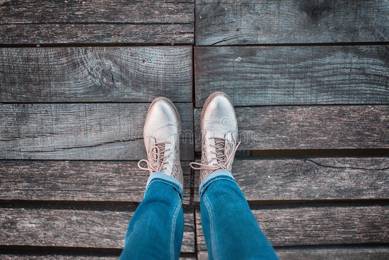 Jambes de femme avec des chaussures sur le bridgeconce en bois photo libre de droits