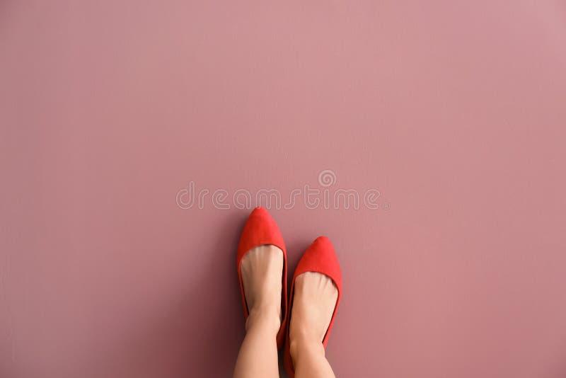 Jambes de femme dans des chaussures élégantes sur le fond de couleur photographie stock libre de droits