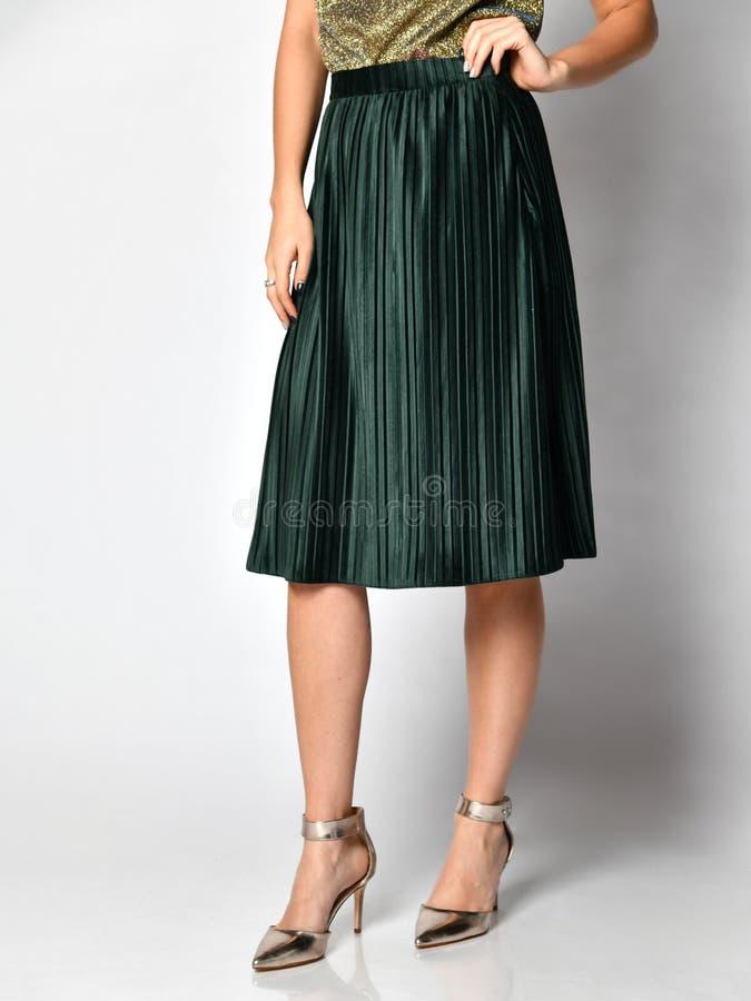 Jambes de femme dans la robe verte de jupe dans des chaussures moyennes argentées de collines sur le gris photos stock