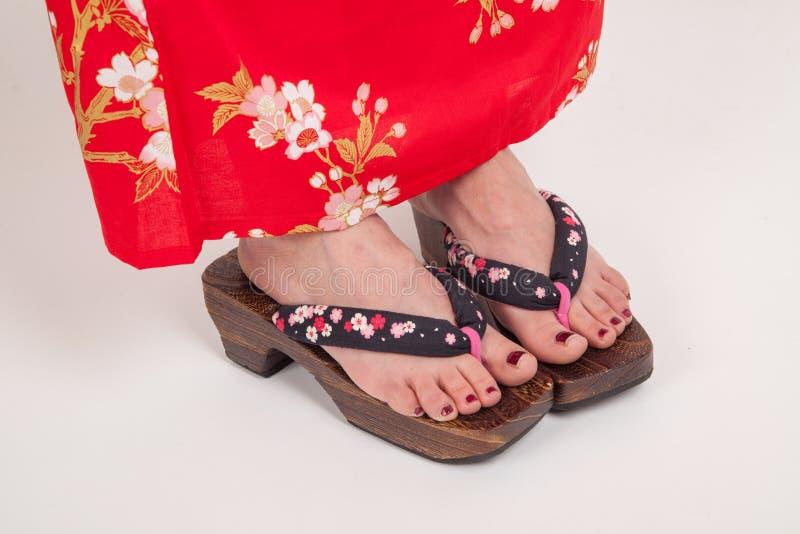 Jambes de femme dans le style japonais de kimono GETA, chaussures ornementales japonaises de zori photo stock