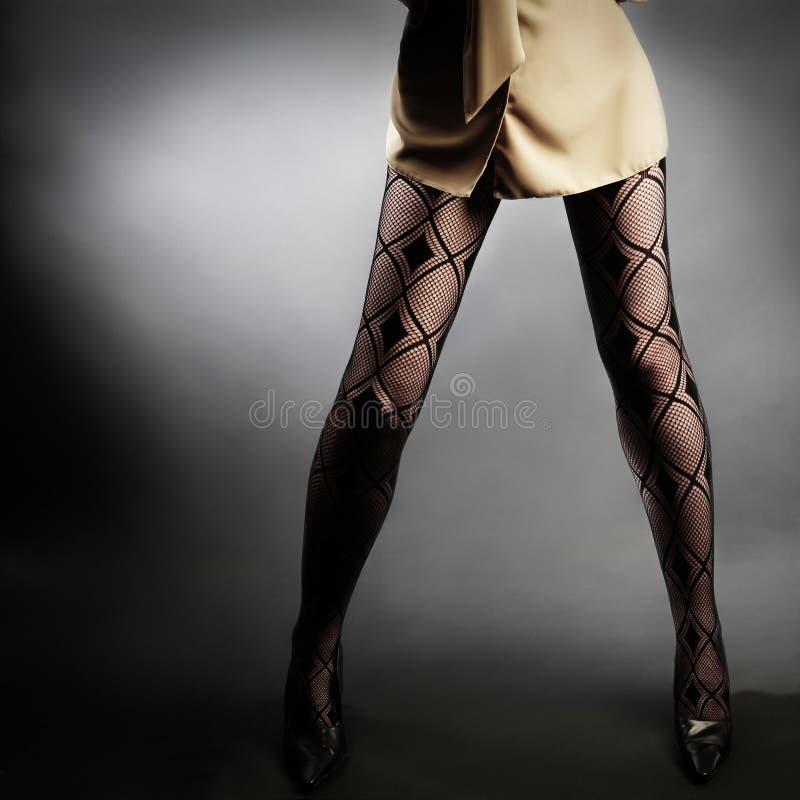 Jambes de femme de bas de filet photographie stock libre de droits
