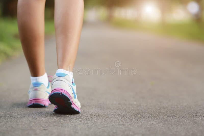 Jambes de femmes marchant sur le chemin et la lumière photo stock