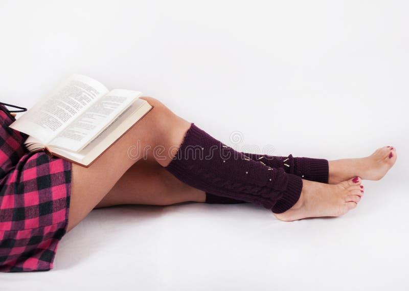 Jambes de fille sur le fond blanc et livre sur des genoux images libres de droits