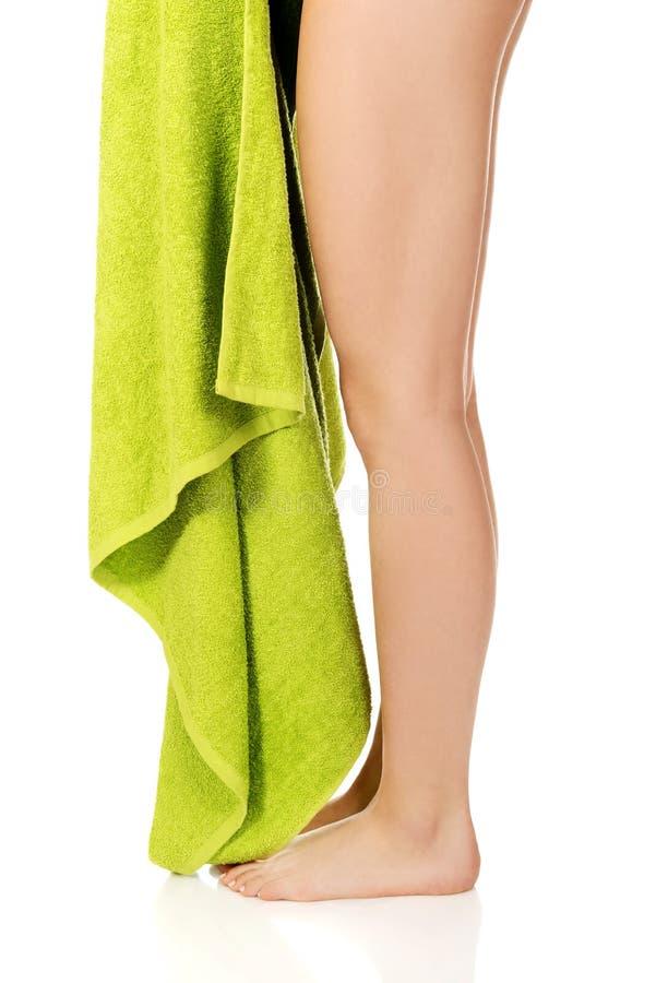 Jambes de jeune femme avec la serviette verte photos libres de droits