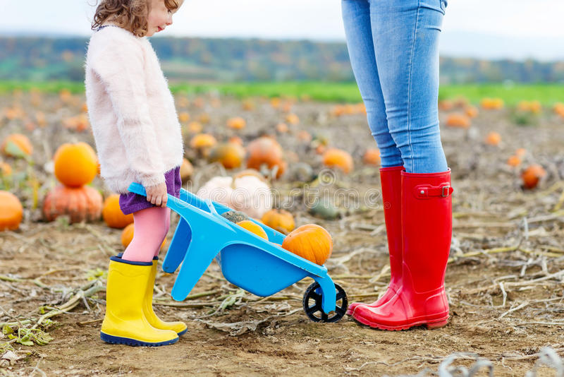Jambes de jeune femme et de son daugher de petite fille dans les rainboots images stock