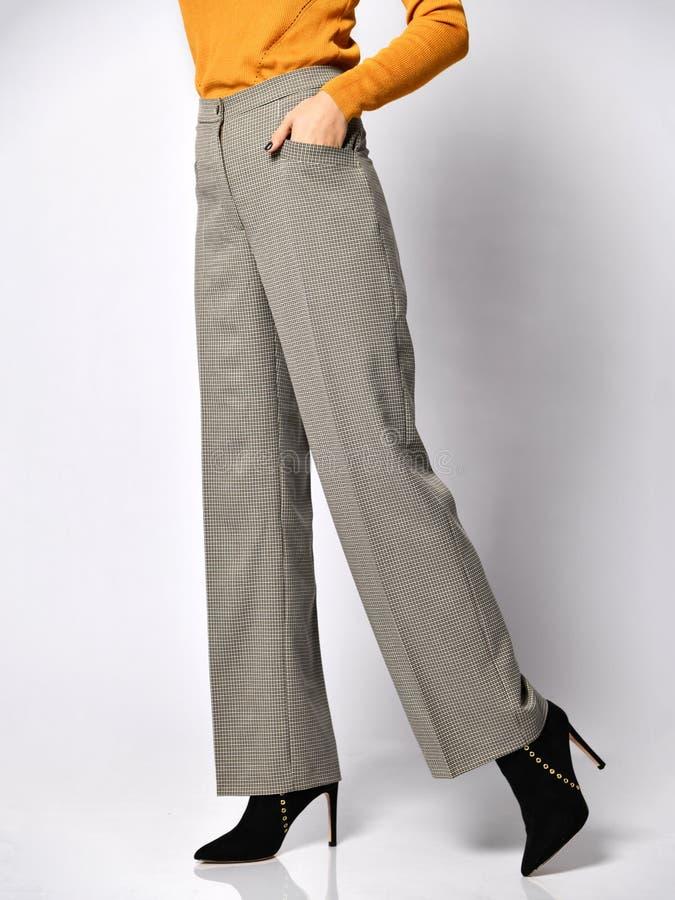 Jambes de jeune femme marchant dans le nouveau pantalon classique gris dans la boîte du costume sur un blanc images libres de droits