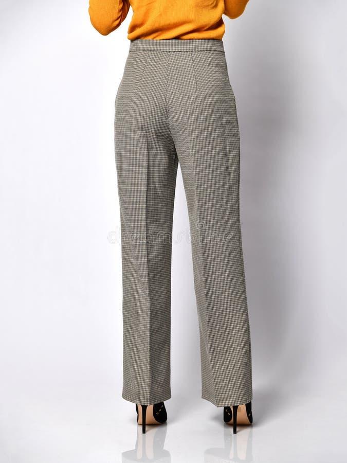 Jambes de jeune femme marchant dans le nouveau pantalon classique gris dans la boîte du costume sur un blanc photo libre de droits