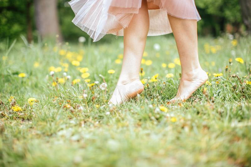 Jambes de jeunes femmes aux pieds nus portant la robe rose se tenant sur une jambe sur l'herbe verte avec les fleurs jaunes, fin  photographie stock libre de droits