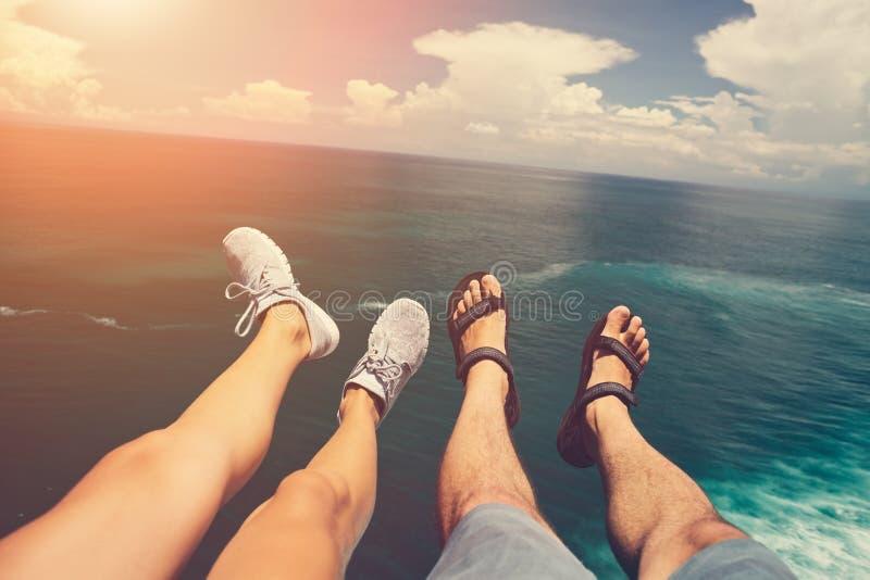 Jambes de l'homme dans les sandales et la femme dans des chaussures de sport se reposant au-dessus de l'océan bleu photo stock