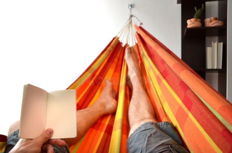 Jambes de l'homme se couchant dans l'hamac lumineux tenant le livre d'avis vide dans sa main image stock