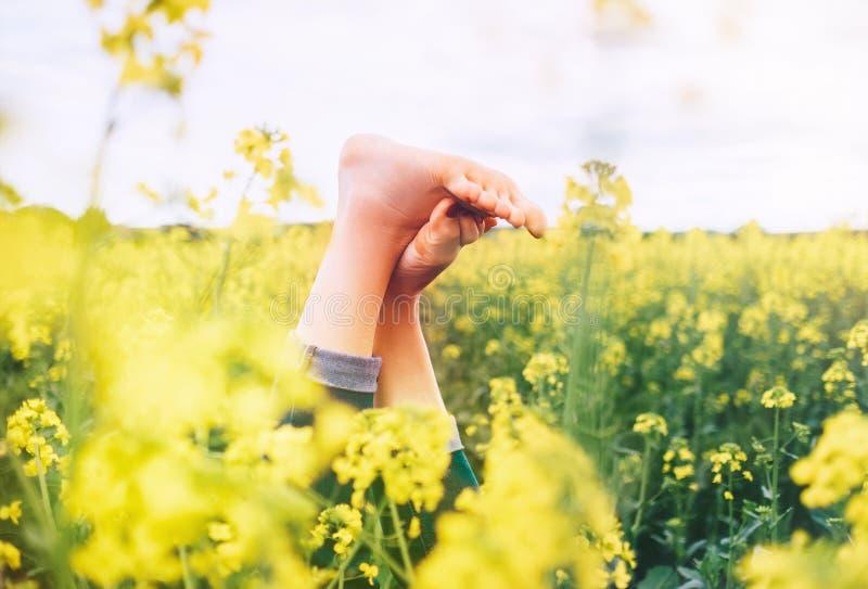 Jambes de la femelle heureuse se situant dans le pré jaune-foncé de fleurs Bonheur dans l'image de concept de nature images stock