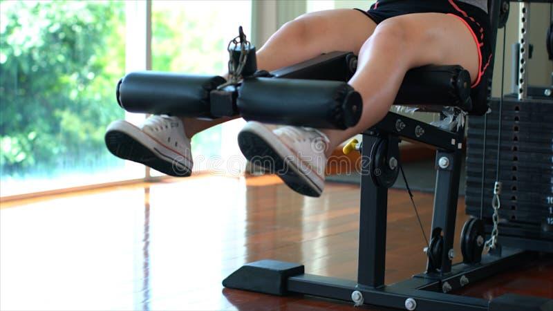 Jambes de la jeune fille de sport faisant les boucles de jambe posées sur la machine en GY image libre de droits
