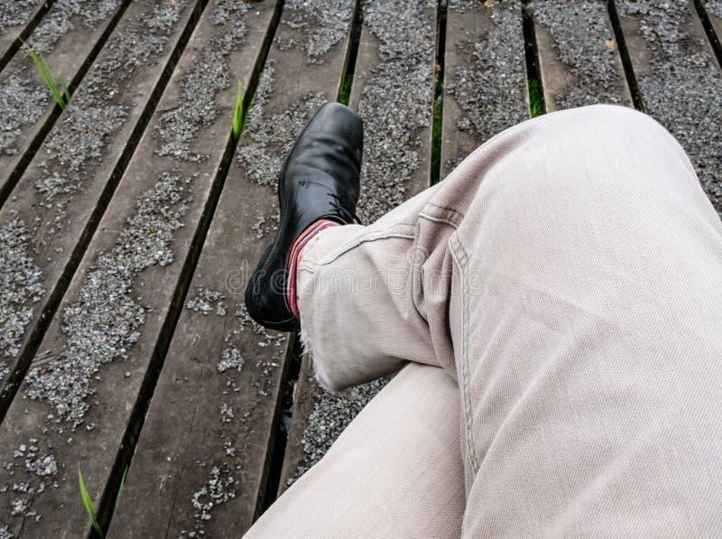 Jambes de mâle adulte vues croisées tout en se reposant sur un banc de parc photographie stock libre de droits