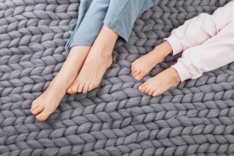 Jambes de mère et de fille sur le plaid tricoté de laine photos stock