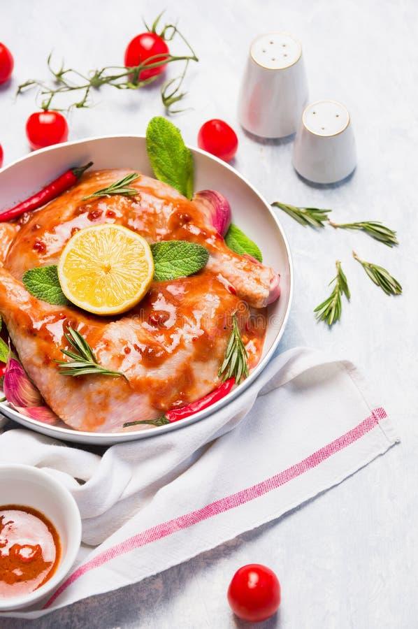Jambes de poulet avec la marinade épicée rouge dans la cuvette blanche images libres de droits