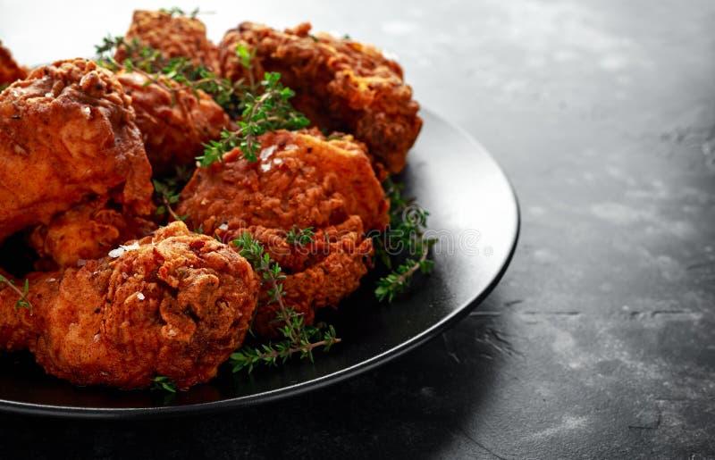 Jambes de poulet croustillantes frites, cuisse dans un plat noir avec des herbes image stock
