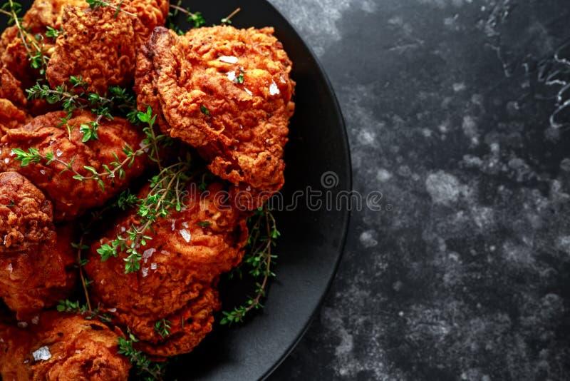 Jambes de poulet croustillantes frites, cuisse dans un plat noir avec des herbes photos stock